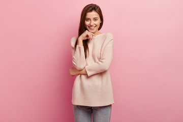 Photo of positive pleasant looking European woman keeps hands partly crossed, smiles gently, looks directly at camera, wears oversized sweater, poses over pink background, talks with friend.