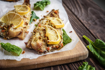 Baked pollock fillet with lemon and spinach on a wooden background