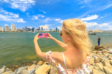 Blonde tourist takes photo of San Diego By skyline by mobile phone with American flag cover. Female lifestyle takes pictures in California summer holidays with her smartphone from Coronado Island, USA