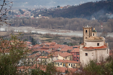 Santo Stefano Magra in Lunigiana area of Italy in La Spezia province. Church, houses and River Magra. Wintry day.
