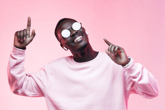 Young smiling african american man listening to music with earphones, dancing isolated on pink background
