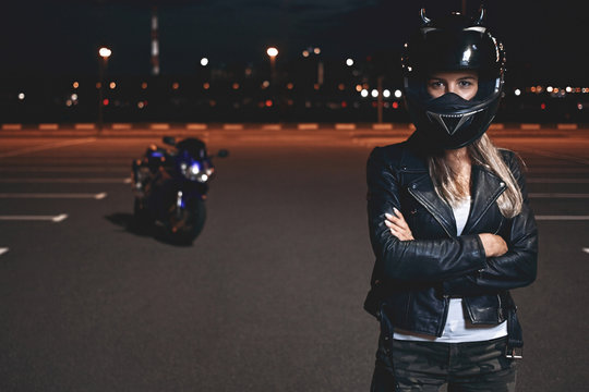 Picture of confident self determined young female rider in safety helmet standing in parking lot keeping arms crossed and looking at camera, going to have ride on motorcycle around night city