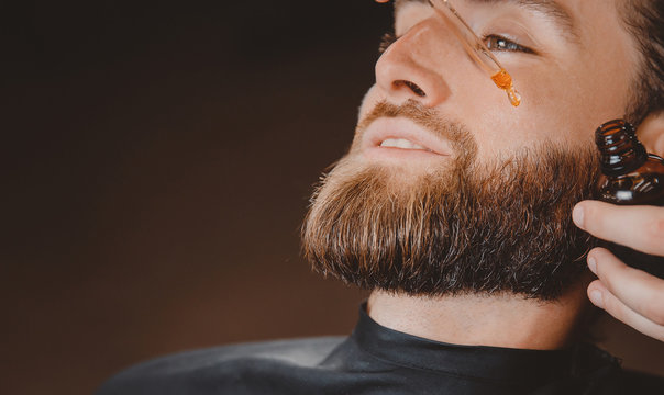 Oil for spa grooming and beard growth for man in a dropper. Concept barbershop