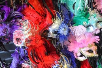 Mardi Gras masks in New Orleans, Louisiana, United States. Various multi-colored masks on display, inlcuding pink, green, red, yellow, and purple.