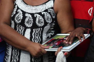 Marilia, mother of soccer player Vinicius de Barros Silva Freitas, holds a picture during his burial, after a deadly fire at Flamengo soccer club's training center, in Volta Redonda