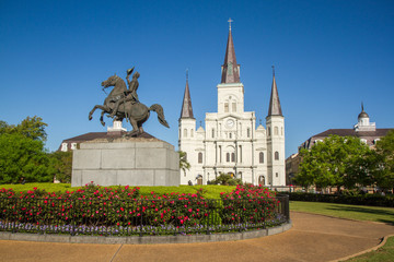 St. Louis Cathedral, Jackson Square, Louisiana, United States. Color horizontal image with Andrew Jackson statue in foreground on left with red flowers.