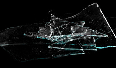 Broken glass pile pieces with water droplets isolated on black background and texture