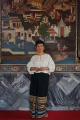 femme devant une peinture décorative dans un temple boudhiste