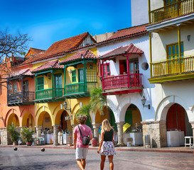 Cartagena, Colombia - January 27, 2019 - Tourists walking narrow colorful streets of Cartagena