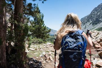 Blond adult female hiker treks through Lundy Canyon near Mammoth Lakes in the Eastern Sierra Nevada mountain range in California