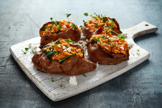 Roast sweet potato stuffed with feta cheese and kale. healthy food