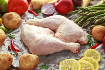 Raw Chicken Legs on baking paper with variety of vegetables