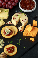 Cheese platter served with grapes, ale chutney, honey, crackers on stone board. Brie, cheddar, red leicester, wensleydale cranberries, blue stilton.