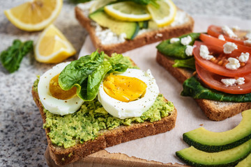 Healthy avocado and egg toasts. Toast, avocado, egg, tomatoes, spinach, cheese Feta, lemon. Organic healthy food. Clean healthy eating