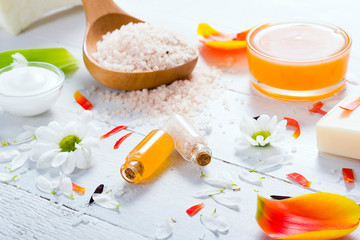 aromatherapy: orange gel and extract, bath salt, cosmetic cream, organic soap and petals on white wood