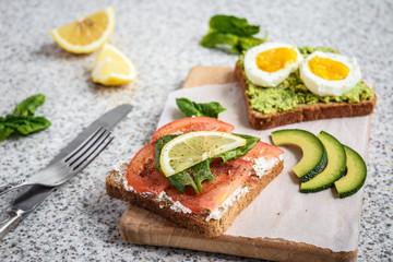 Healthy avocado and egg toasts. Toast, avocado, egg, tomatoes, spinach, cheese Feta, lemon. Organic healthy food. Clean healthy eating