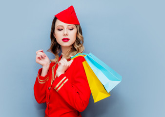 stewardess wearing in red uniform with shopping bags