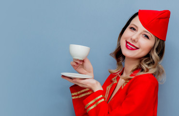stewardess wearing in red uniform with cup of coffee or te