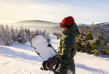 Girl snowboarder stands with snowboard on mountain's top. Ski resort Wall mural