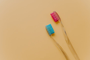 Two blue and red plastic toothbrushes isolated over yellow background with empty space aside for your promotion. Isolated objects