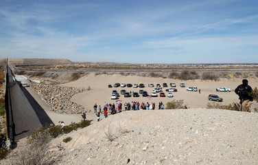 U.S. demonstrators holding U.S. flags gather at the open border to make a human wall in support of the construction of the new border wall between the U.S. and Mexico, in Ciudad Juarez