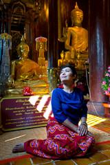 Femme en costume traditionnel assise dans un temple