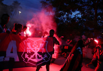 Fans with flares walk outside Maracana Stadium to honor fire victims at Flamengo's training centre