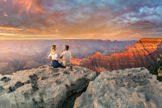 Man and woman sit on the edge of the rim having great conversation during the Grand Canyon sunset