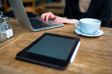 young adult businessperson working on laptop with coffee pro pad and pencil on the table