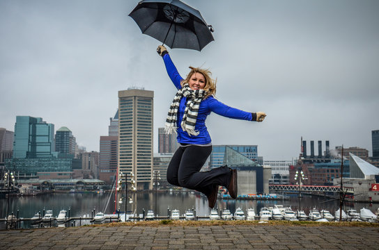 Woman jumps with an umbrella on a foggy cloudy day in Baltimore at Federal Hill Park