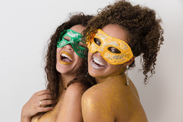 Two beautiful young women with their bodies painted in gold. Young African-American women dressed up as masks and with their bodies painted for the carnival.