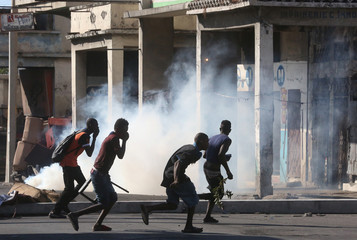People run away from tear gas during clashes at a protest against the government in a street of Port-au-Prince