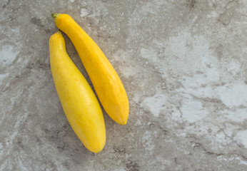 two ripe yellow summer squash on a gray marble countertop with copy space