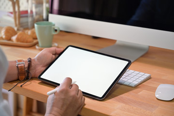 Creative designer working with tablet device on wooded office workspace