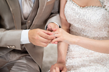 The groom put a wedding ring into a bride finger inThai Wedding Concept