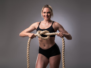 Muscular woman with heavy ropes