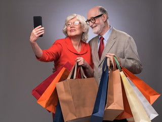 Senior couple taking selfie after shopping