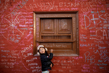 A girl looks towards her father as she writes on the wall of a Saraswati temple during the Shreepanchami festival in Kathmandu
