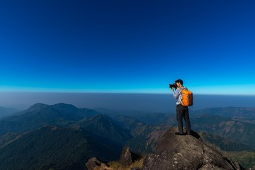 Photographer takes a picture while standing on the mountain peak at strong wind .Travel Concept