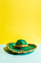 Mexican sombrero hat on geometric yellow and green pastel tone background.