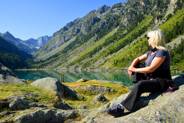 Tourist sitting on rock at Gaube lake. Hautes Pyrenees, France.