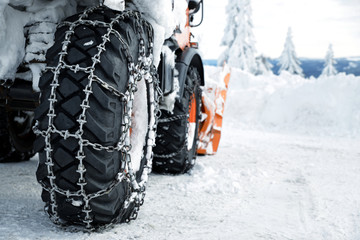 Car wheels equipped with snow chains. Winter season.