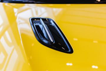 Chrome yellow car design elements - air intake on the bonnet, soft focus