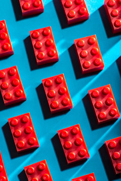 Red plastic geometric cubes contrasted on blue background. Construction toys on geometric shapes. Arranged in rows.