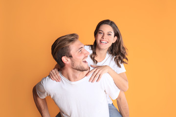 Image of caucasian couple looking at each other and smilling while sitting on back of content man isolated over yellow background.