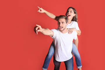 Lovely couple smiling together and pointing away while sitting on back of content man over red background.