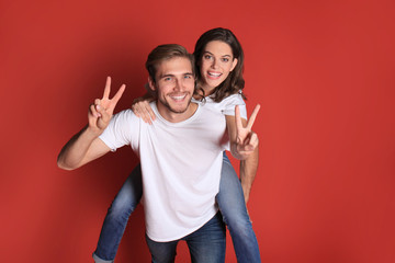 Lovely couple smiling together and showing peace away while sitting on back of content man over red background.