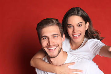 Happy young couple while sitting on back of content man isolated over red background, taking a selfie.