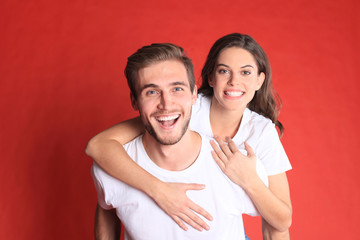 Lovely couple smiling together while sitting on back of content man over red background.