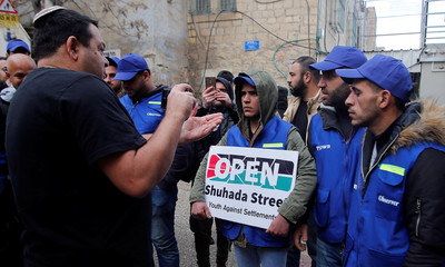 Jewish settler takes pictures of Palestinian activists during a protest in Hebron, in the Israeli-occupied West Bank